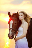 Красивая женщина ехать лошадь на заходе солнца на пляже Молодое gir Стоковое Изображение RF