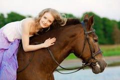 Красивая женщина ехать лошадь на заходе солнца на пляже Молодое gir Стоковые Фотографии RF