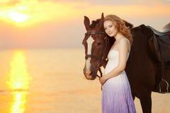 Красивая женщина ехать лошадь на заходе солнца на пляже Молодое gir Стоковые Изображения