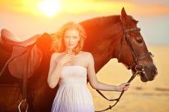 Красивая женщина ехать лошадь на заходе солнца на пляже Молодое gir Стоковые Изображения RF