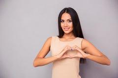 Красивая женщина делая сердце с пальцами Стоковое Фото