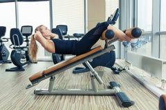 Красивая женщина делая тренировку фитнеса прессы на спортзале спорта Стоковое Изображение