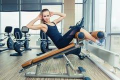Красивая женщина делая тренировку фитнеса прессы на спортзале спорта Стоковые Изображения