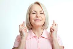 Красивая женщина закрыла ее глаза и делать желание пересекл пальцы на белой предпосылке стоковая фотография rf