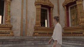 Красивая женщина идет около виска Будды в chalong wat Sightseeing сток-видео