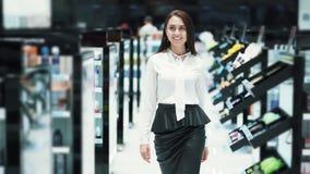 Красивая женщина идет среди полок в косметиках ходит по магазинам, замедленное движение, снятое steadicam акции видеоматериалы