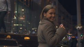 Красивая женщина идя на освещенную улицу города, подмигивая и flirting, счастье акции видеоматериалы