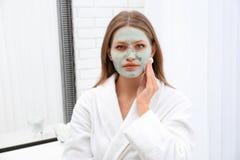 Красивая женщина извлекая домодельную маску глины из ее стороны стоковая фотография
