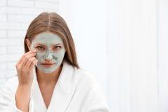 Красивая женщина извлекая маску глины из ее стороны стоковое фото