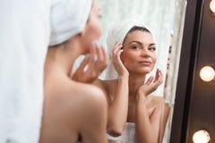 Красивая женщина изнеживая ее кожу стоковая фотография rf