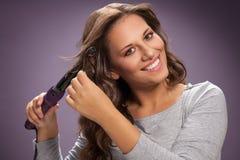 Красивая женщина используя завивая утюг на ее волнистых волосах стоковые фото