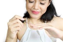 Красивая женщина используя маникюр на студии Стоковая Фотография