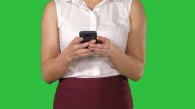 Красивая женщина используя руки отправляя SMS по умному телефону на зеленом экране, ключ женщин мобильного телефона Chroma сток-видео
