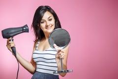 Красивая женщина используя фен для волос и усмехающся пока смотрящ зеркало на розовой предпосылке стоковое изображение rf