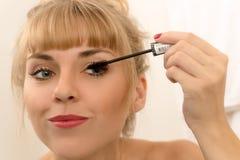 Красивая женщина используя карандаш для глаз туши Стоковые Изображения RF