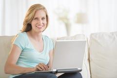 Красивая женщина используя компьтер-книжку на софе Стоковое Изображение