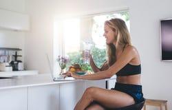 Красивая женщина используя портативный компьютер в кухне Стоковые Изображения