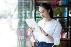 Красивая женщина используя цифровую таблетку в кафе Стоковое Изображение
