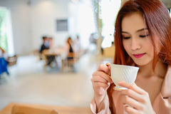 Красивая женщина и держать чашку кофе в ее руке в кофейне предпосылки нерезкости Стоковое Фото