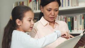 Красивая женщина и ее маленькая дочь читая книгу на библиотеке стоковая фотография rf