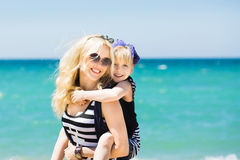 Красивая женщина и ее очаровательная дочь отдыхая на пляже Стоковые Фотографии RF
