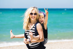 Красивая женщина и ее очаровательная дочь отдыхая на пляже Стоковое Изображение