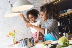 Красивая женщина и ее дочь варя в кухне Стоковая Фотография