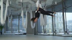 Красивая женщина кантует в воздухе держа дальше гамак йоги в студии Много белых пустых гамаков вокруг самомоднейше сток-видео