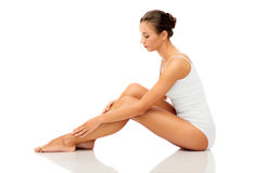 Красивая женщина касаясь ее ровным чуть-чуть ногам стоковое изображение rf