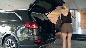 Красивая женщина кладя багаж в черный виллис Женский путешественник подготавливая задействовать акции видеоматериалы