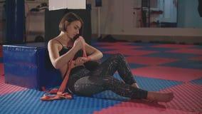 Красивая женщина кладя на красные пробивая обручи в студию фитнеса в 4 k акции видеоматериалы