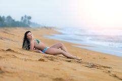 Красивая женщина лежа на песке на пляже летом Женщина счастья летних каникулов беспечальная радостная стоковое фото rf