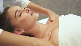Красивая женщина лежит на таблице массажа и получает роскошное обслуживание заботы кожи тела сток-видео