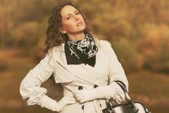 Красивая женщина моды в белый идти пальто канавы на открытом воздухе стоковые фото