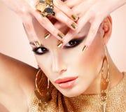 Красивая женщина моды с черным составом и золотым маникюром Стоковые Изображения RF