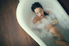 Красивая женщина наслаждаясь ванной Стоковая Фотография