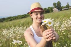 Красивая женщина наслаждаясь маргариткой в поле Стоковая Фотография