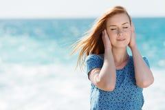 Красивая женщина наслаждаясь морским бризом стоковое изображение