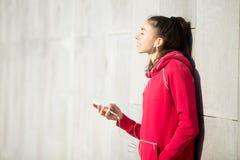 Красивая женщина наслаждаясь музыкой в ее игроке телефона Стоковое Фото