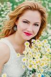 Красивая женщина наслаждаясь полем маргаритки весной Стоковые Изображения