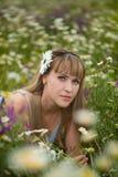 Красивая женщина наслаждаясь полем маргаритки, славной женщиной лежа вниз в луге цветков, милый ослаблять девушки внешний, имеющ  Стоковое Изображение