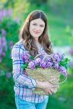 Красивая женщина наслаждаясь садом сирени, молодой женщиной с цветками в зеленом парке девушка срывая сирень в саде стоковое изображение