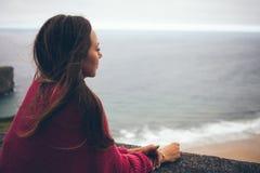 Красивая женщина наслаждаясь хитростью вида на море идя самостоятельно на лето e Стоковые Изображения RF