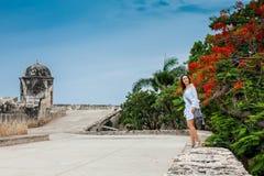 Красивая женщина на белом платье идя самостоятельно на стены окружая колониальный город Cartagena de Indias стоковое изображение rf