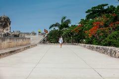 Красивая женщина на белом платье идя самостоятельно на стены окружая колониальный город Cartagena de Indias стоковые изображения rf