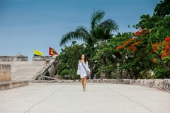 Красивая женщина на белом платье идя самостоятельно на стены окружая колониальный город Cartagena de Indias стоковые изображения