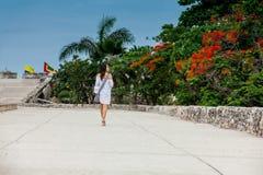 Красивая женщина на белом платье идя самостоятельно на стены окружая колониальный город Cartagena de Indias стоковое фото rf