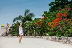 Красивая женщина на белом платье идя самостоятельно на стены окружая колониальный город Cartagena de Indias стоковое фото
