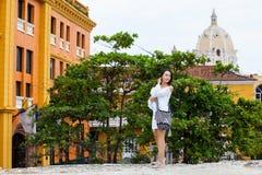 Красивая женщина на белом платье идя самостоятельно на стены окружая колониальный город Cartagena de Indias стоковая фотография