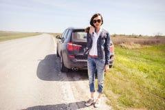 Красивая женщина на дороге около сломленного автомобиля Стоковые Фотографии RF